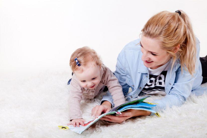 maman et bébé regardent un livre en riant